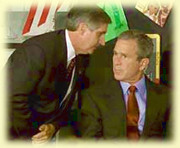 Andrew Card whispers something to President Bush after the second planes strikes the WTC